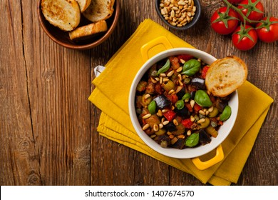 Traditional Italian caponata, served with croutons in a yellow, sunny pot. Decorated with basil and pine nuts. Top view.