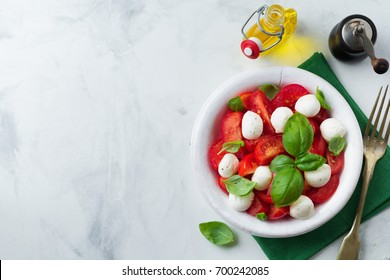 Traditional Italian caprese salad with tomatoes, mozzarella cheese and basil on a light marble background in a white old ceramic plate. Selective focus.Top view. Copy space.