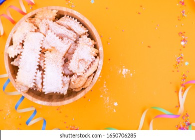 Traditional Italian carnival fritters dusted with icing sugar - frappe or chiacchiere . Sweets and festive decor on a yellow background. Free space for text