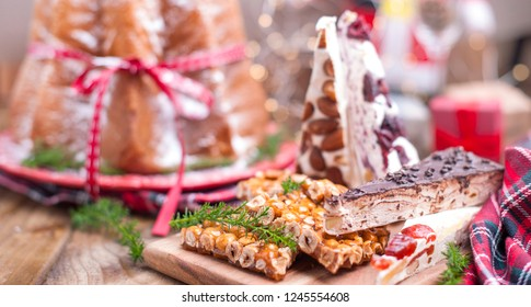 Traditional Italian Christmas fruit cake Panettone Pandoro with festive red ribbon and sweets from nuts and nougat. On a wooden background. Free space for text