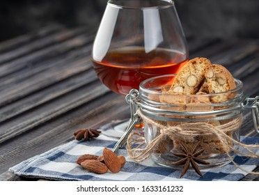 Traditional italian Christmas New Year dry cookies biscuits biscotti cantuccini. Biscotti di Prato with dessert wine. In glass jar.