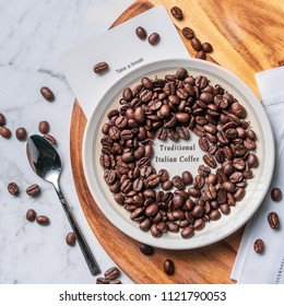 Traditional Italian Coffee beans are scattered around a white saucer and wooden chopping board, with stainless steel spoon.