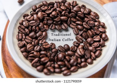 Traditional Italian Coffee beans are scattered around a white saucer and wooden chopping board.