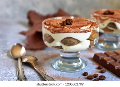 Traditional italian coffee dessert tiramisu with biscuit and mascarpone cheese in a glass on a light grey slate, stone or concrete background.