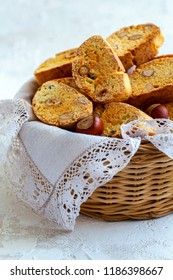 Traditional Italian cookies with almonds and hazelnuts in a wicker basket with linen napkin on a textured white table, selective focus.
