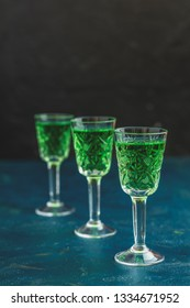 Traditional italian or czech liqueur or bitter with fennel. Three absinthe glass. Dark blue concrete table surface background, copy space for you text.