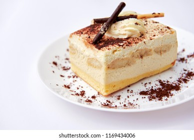 Traditional italian dessert tiramisu/ tiramisu cake with cream mascarpone and cacao powder on a white plate. White background. Close up. Isolated.