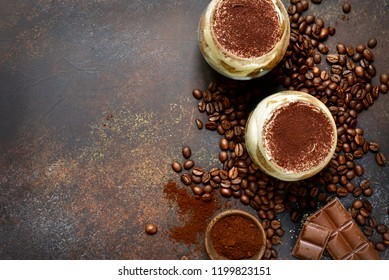 Traditional italian dessert tiramisu with mascarpone and biscuit in a glasses over dark slate, stone or concrete background.Top view with copy space.