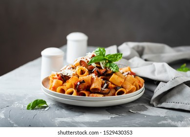 Traditional Italian dish pasta alla norma with eggplant and ricotta, selective focus