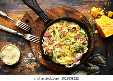 Traditional italian dish spaghetti carbonara with bacon in a cream sauce in a skillet over dark wooden background.Top view with copy space.