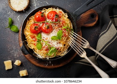 Traditional Italian dish of spaghetti with tomato sauce and parmesan cheese in iron frying pan on dark old concrete background. Selective focus. Top view.