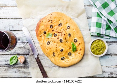 Traditional Italian Focaccia with black olives and rosemary - homemade flat bread focaccia over wooden background, top view