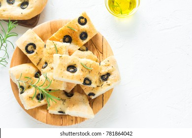 Traditional Italian Focaccia with  black olives and rosemary - homemade flat bread focaccia on white, top view and copy space