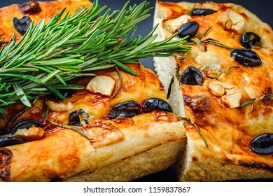 Traditional Italian Focaccia with olives, garlic and rosemary, homemade bread close up