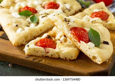 Traditional Italian Focaccia with rosemary, tomatoes and feta - close-up homemade flat bread focaccia.