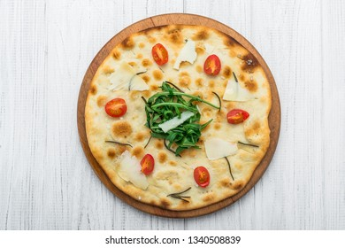 Traditional Italian Focaccia with tomatoes, black olives and rosemary - homemade flat bread focaccia. On a wooden table