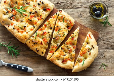 Traditional Italian Focaccia with tomatoes, black olives and rosemary - homemade flat bread focaccia