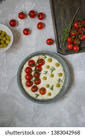 Traditional Italian focaccia with tomatoes, olives and rosemary. Focaccia cooking process, ingredients. Focaccia dough.