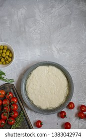 Traditional Italian focaccia with tomatoes, olives and rosemary. Focaccia cooking process, ingredients. Focaccia dough. Space for text.