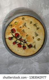 Traditional Italian focaccia with tomatoes, olives and rosemary. Baked focaccia in a baking tray. Round form. The process of making focaccia.
