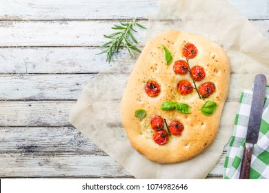 Traditional Italian Focaccia with tomatoes and rosemary - homemade flat bread focaccia over wooden background, top view