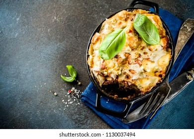 Traditional italian food, homemade lasagna with fresh basil, dark blue background copy space