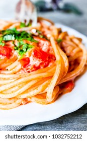 Traditional italian food. Pasta spaghetti with vodka cream sauce, tomatoes, basil served with fresh parsley in a white plate on a wooden table, selective focus. Comfort food. Hearty food.