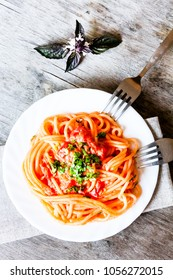 Traditional italian food. Pasta spaghetti alla vodka with cream sauce, tomatoes, parsley and basil on a plate on a wooden table, selective focus. Comfort food. Vegetarian style pasta.