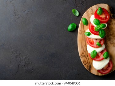 Traditional italian food, sliced tomatoes and mozzarella on a wooden board made of olive tree, dark stone background. Top view, copyspace