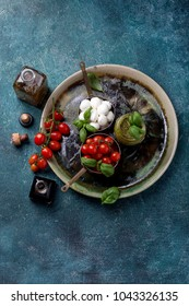 Traditional Italian fresh salad Caprese made of organic cherry tomatoes and mini mozzarella di Bufalla served in the rustic ceramic plate over stone background. Healthy and traditional food concept.