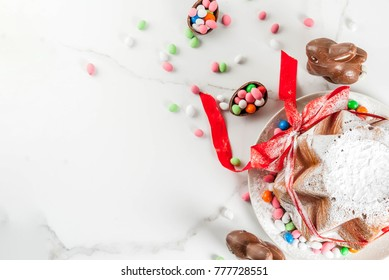 Traditional Italian fruit cake Panettone Pandoro with festive red ribbon, Easter rabbits and sweet candy eggs decorations, on wooden home background, copy space top view