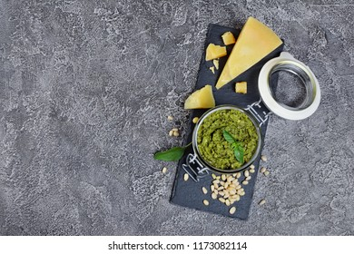 Traditional italian green sauce pesto in glass jar with parmesan cheese, pine nuts and basil leaves on black slate board and gray concrete background