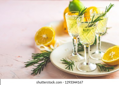 Traditional italian homemade lemon alcohol drink liqueur limoncello with pieces of lemon and rosemary herb on light pink, peach or coral color stone concrete surface