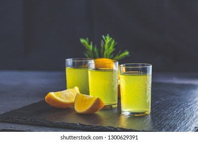 Traditional italian homemade lemon alcohol drink liqueur limoncello with pieces of lemon and rosemary herb on black stone concrete surface.