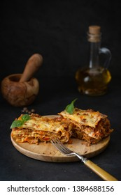 Traditional italian lasagna with vegetables, basil, minced beef meat, tomato and cheese on concrete background.