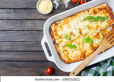 Traditional italian lasagna with vegetables, minced meat and cheese. On a wooden background. Top view, copy space