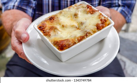 Traditional Italian lasagna with vegetables, minced meat and cheese Served on White Plate With Older Hand - Halal food in Bangkok Restaurant Thailand.