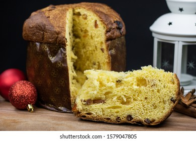 traditional Italian panettone, a typical Christmas dessert. on a wooden cutting board with red Christmas balls, a white lantern and a tin box