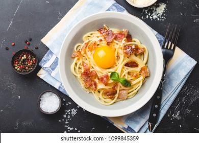 Traditional Italian pasta dish, spaghetti carbonara with yolk, parmesan cheese, bacon in plate on black rustic stone background, top view. Italian dinner with pasta