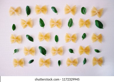 Traditional Italian pasta pattern. Raw farfalle pasta with basil leaves on a white background. Dry uncooked pasta on a white board. Top view.