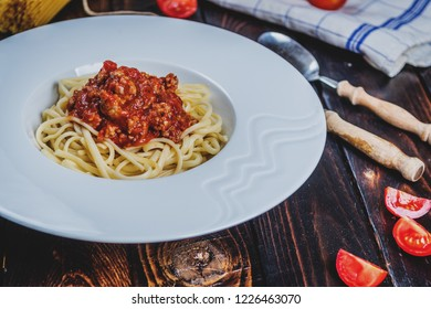Traditional Italian pasta spaghetti bolognesse with minced meat and tomatoes and raw spaghetti on dark wood table