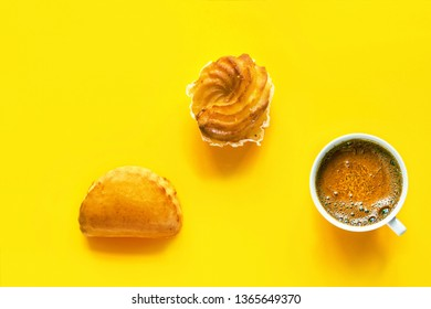 Traditional Italian pastry cassatella sweet ravioli with ricotta filling zeppole cup of freshly brewed coffee with foamy crema on bright yellow background. Top view flat lay