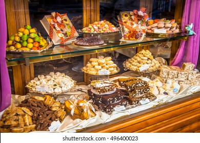 Traditional Italian Pastry shop glass display with selection of nougat, cookies, cake and sweets