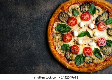 Traditional Italian pizza with eggplants, mozzarella, basil and tomatoes on a dark background top view copy space.