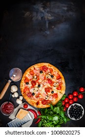 Traditional Italian pizza on a dark table with ingredients. Pizza menu. Space for text.