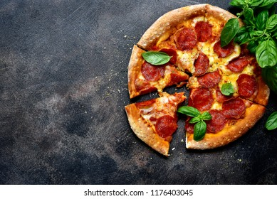 Traditional italian pizza pepperoni with salami and cheese on a dark slate, stone, metal or concrete background.Top view with copy space.