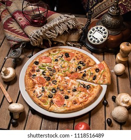 Traditional Italian pizza, vegetables, ingredients on a dark wooden background. Pizza is cooking in the oven. Pizza menu. View from above. Space for text.