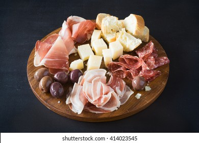 Traditional italian plate with  prosciutto crudo, salami, parmesan cheese, olives and bread. Selective focus.