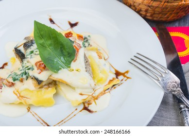 traditional Italian ravioli with sea bass fillet served on a plate on a wooden table with decor