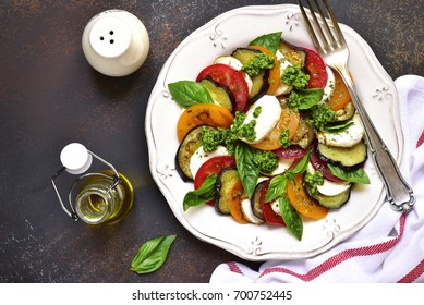 Traditional italian salad caprese with eggplants on a vintage plate over dark slate,stone or concrete background.Top view.